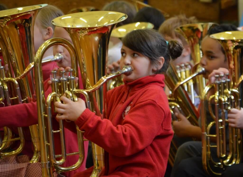 Artsmark St George's Primary School pupil playing the trombone