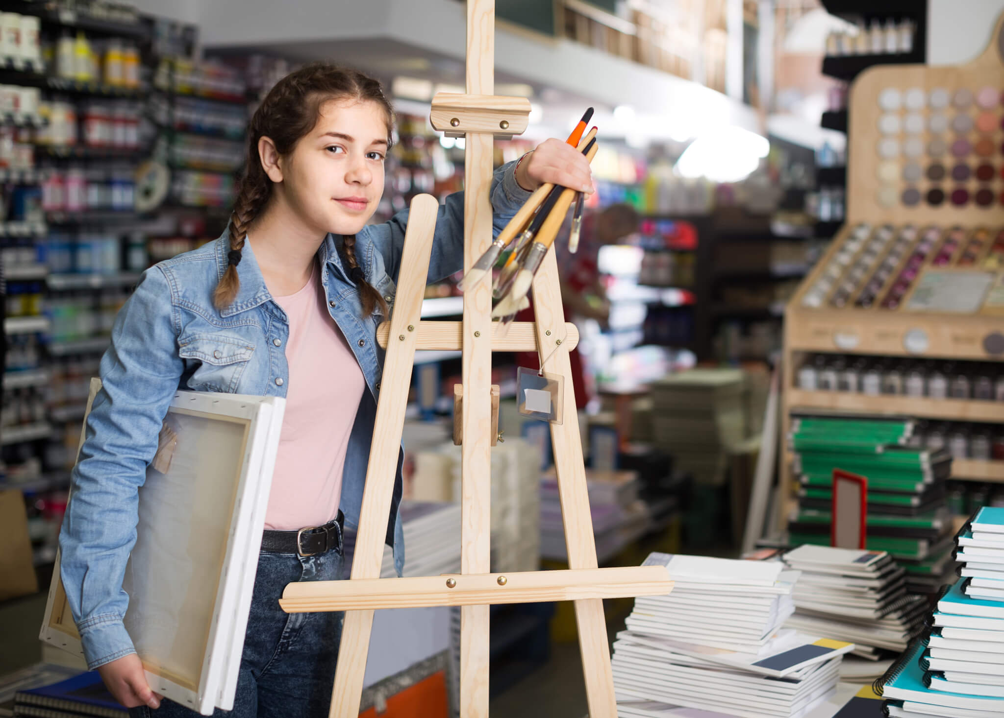 Teen girl holding supplies for painting in hands in art department