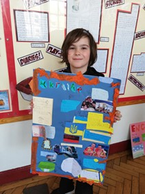 Pupil from Porter Croft Primary holding up a board titled 'Ukraine' with various clippings and images attached.