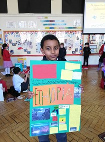 Pupil from Porter Croft Primary holding up a board titled 'Ethiopia' with various clippings and images attached.