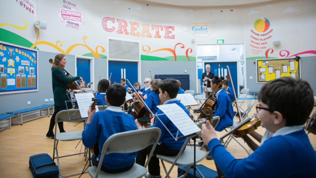 A group of pupils playing musical instruments in a classroom.