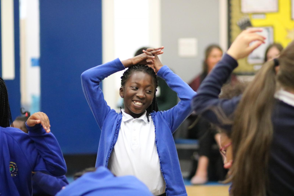 A picture of a pupil at school moving with their hands over their head