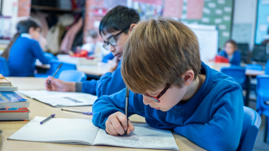 A picture of a pupil at school drawing int a notebook